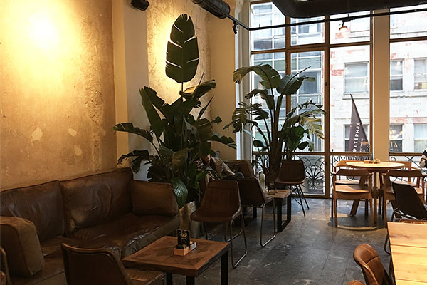 Comfortable sofas and coffee group pods are differentiated by loose rugs sitting on the tiled floor with old brick walls adding to the sense of home atmosphere.