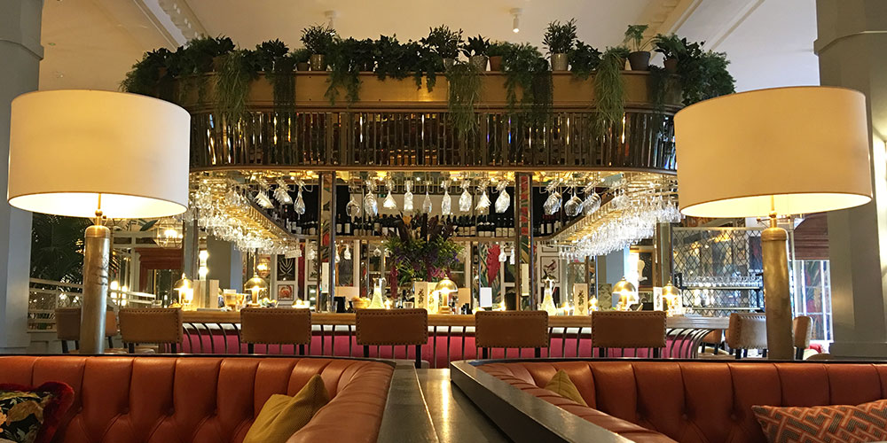 Brighton Ivy restaurant Architects used comfortable leather banquettes and contrasting bright cushions, cut wall mirrors, inlaid marble floor and the tropical foliage of the potted palms to create classic brasserie restaurant.