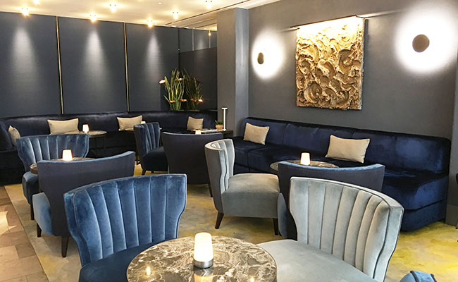 Mere Restaurant bar designers used a combination of petrol blue velvet and pale grey accent  lounge chairs against silk paneled walls with brass edging.
