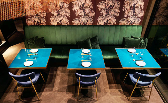 restaurant interior architects of Nishiki used green velvet upholstery and teal blue table tops to deliver sophisticated asian restaurant in Milan
