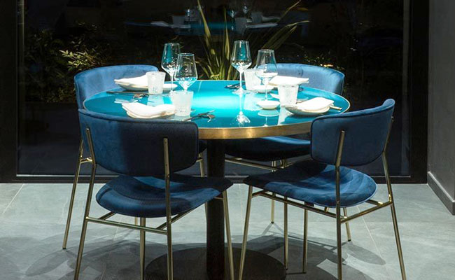 blue dining table with antique brass edge