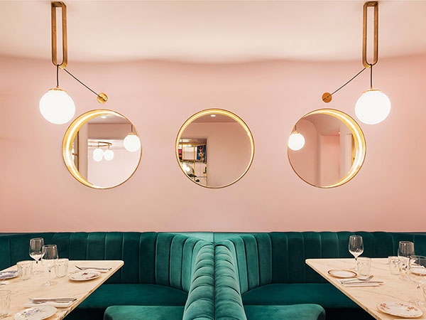 three round mirrors recessed into the wall to create an illusion of windows and the depth to the otherwise small narrow space of North Audley Canteen trendy basement bar